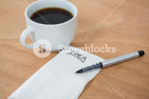 Black coffee with idea written on tissue paper