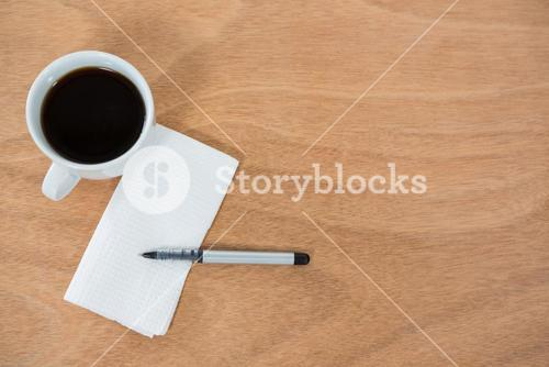 Black coffee with tissue paper and pen