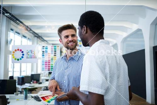 Graphic designer discussing over color swatch with a colleague