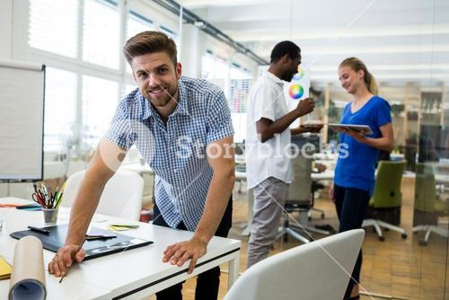 Graphic designer smiling at camera in background