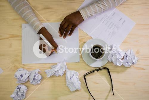 Close-up of graphic designer writing on a paper at his desk