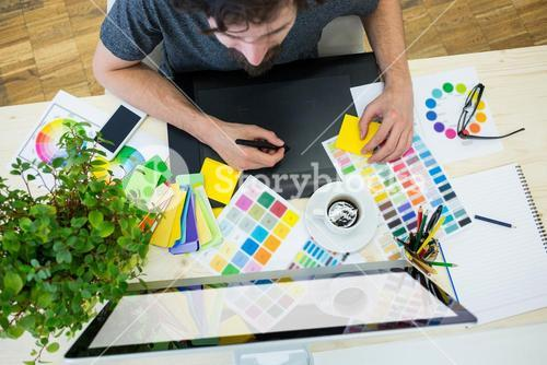 Graphic designer working on graphic tablet at his desk