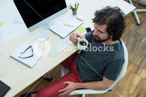 Business executive having coffee at his desk