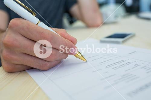 Business executive writing on a document