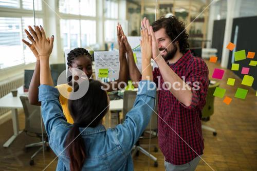 Team of business executives giving high five