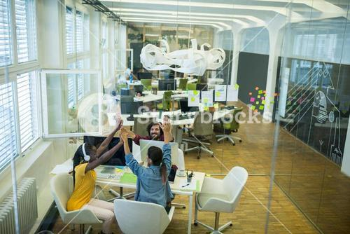 Team of business executives giving high five at desk