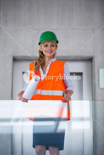 Architect woman in hardhat holding blueprints in corridor