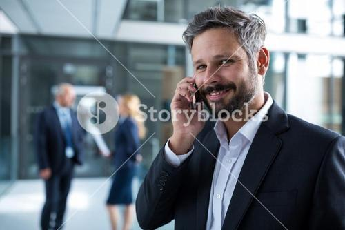 Smiling businessman talking on mobile phone in office corridor