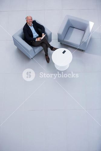 Businessman sitting on sofa with digital tablet and looking up