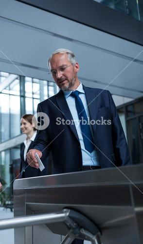 Businessman scanning his card at turnstile gate