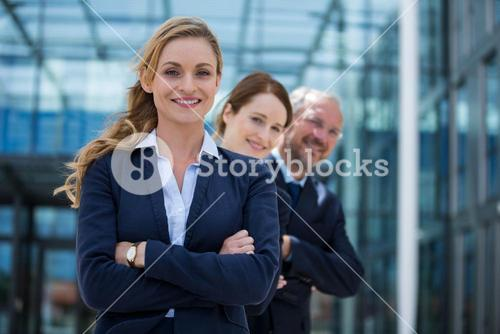 Happy businesspeople standing with their hands folded