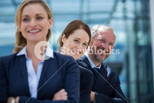 Smiling businesspeople standing with hands crossed