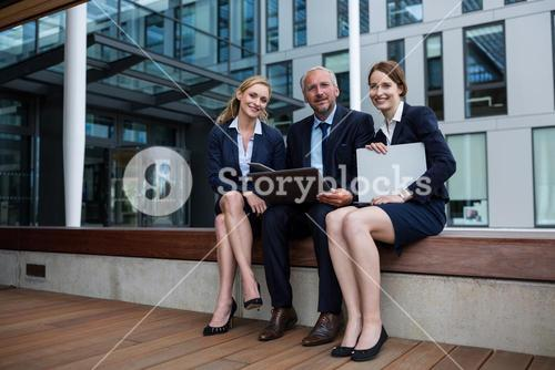 Businesspeople sitting with laptop in office premises