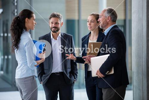 Businesspeople having a discussion in office corridor