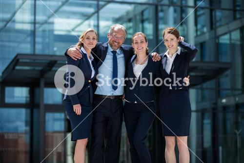 Happy businesspeople standing in office premises