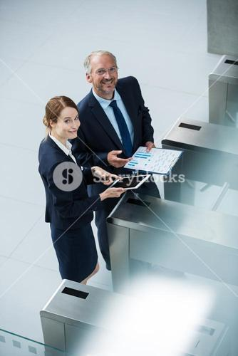 Businessman standing with colleague at turnstile gate