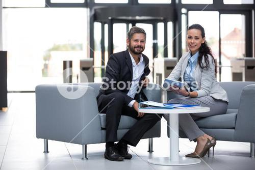 Businessman and colleague sitting in office