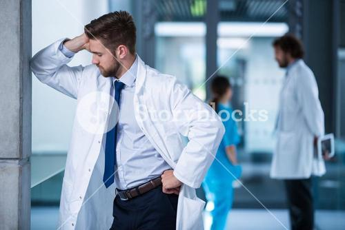 Stressed doctor standing in hospital