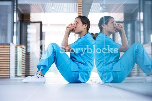 Worried nurse sitting on floor