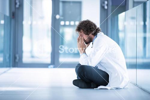 Worried doctor sitting on floor