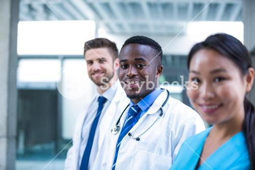 Confident doctor standing with colleagues
