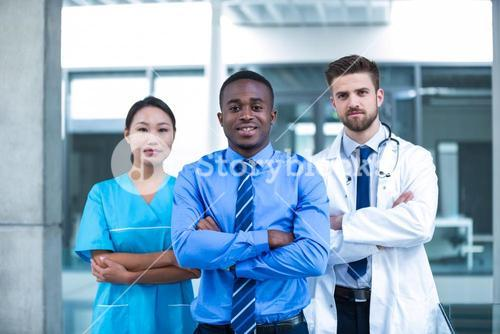 Nurse and doctor with businessman standing in hospital