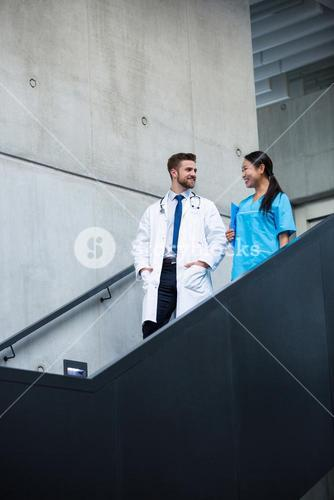 Doctor and nurse walking on stairs and talking
