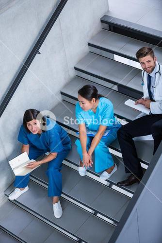 Nurses and doctor talking on stairs