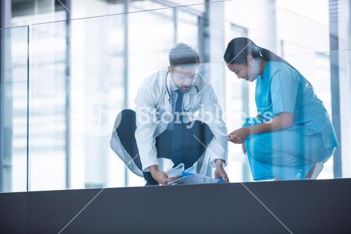 Doctor and nurse collecting fallen medical reports from floor