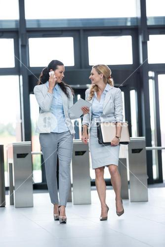 Businesswoman walking with colleague while talking on mobile phone