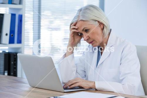 Tense female doctor working on her laptop
