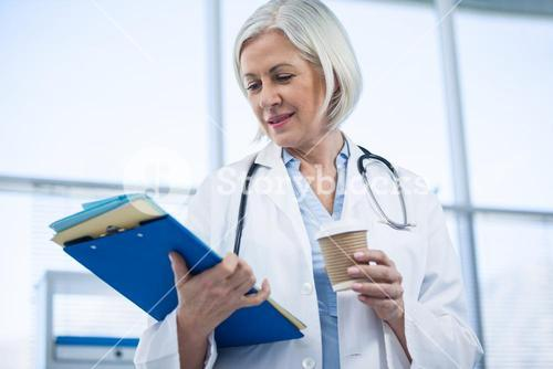 Female doctor holding medical file and coffee cup
