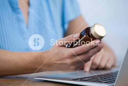 Doctor maintaining record of medicine in laptop