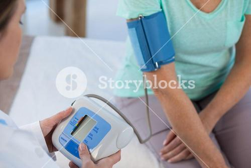 Female doctor checking blood pressure of a patient
