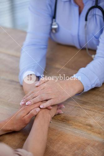 Female doctor consoling patient