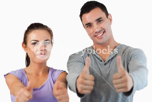 Young couple giving thumbs up