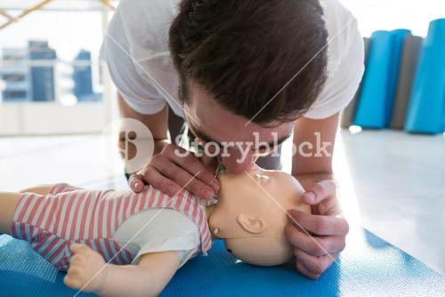 Paramedic practising resuscitation mouth to mouth on dummy