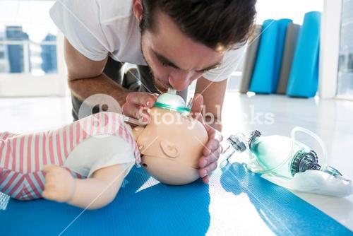 Paramedic blowing oxygen to dummy