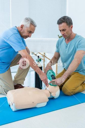 Paramedics practicing cardiopulmonary resuscitation on dummy