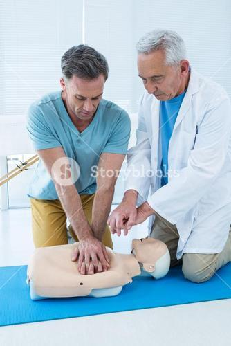Paramedics training cardiopulmonary resuscitation to man