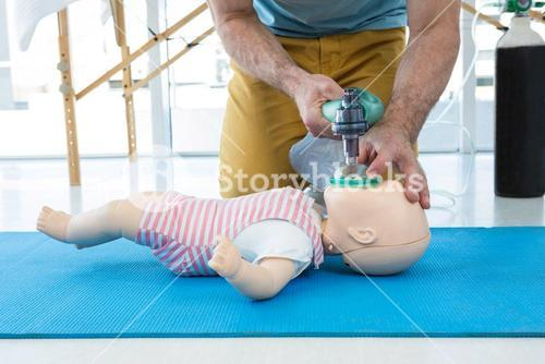 Paramedic practicing cardiopulmonary resuscitation on dummy