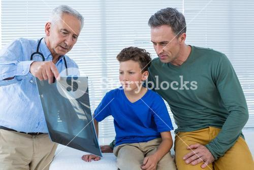 Doctor showing x-ray report to patient and his parent
