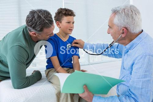 Father looking at son while being examined by doctor