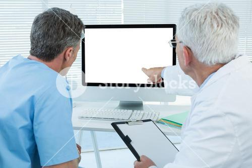 Surgeon and doctor discussing over personal computer