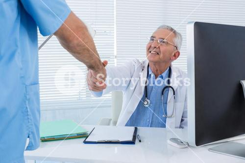 Doctor and surgeon shaking hands