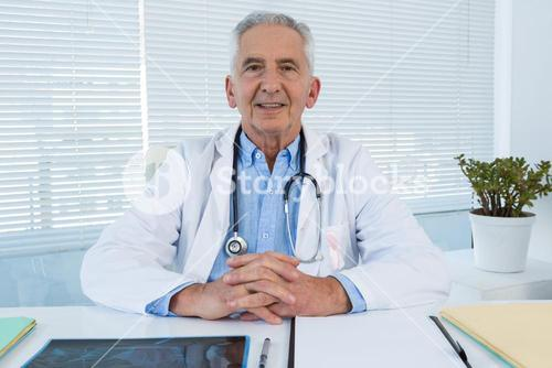 Portrait of smiling doctor sitting at table