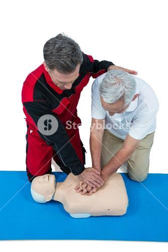 Paramedic training cardiopulmonary resuscitation to senior man