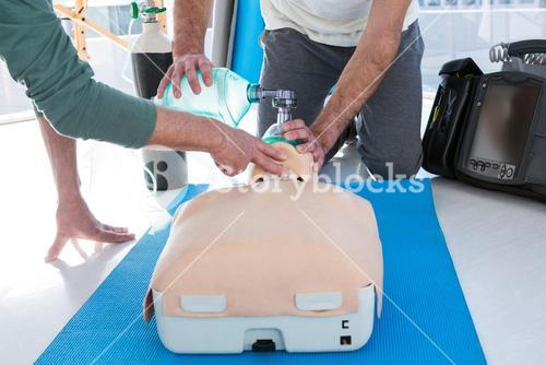 Paramedics practicing cardiopulmonary resuscitation on mannequin