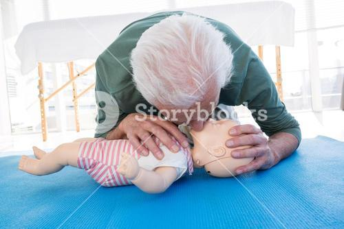 Paramedic practicing resuscitation mouth to mouth on dummy