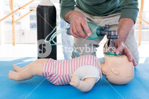 Paramedic practicing resuscitation on dummy
